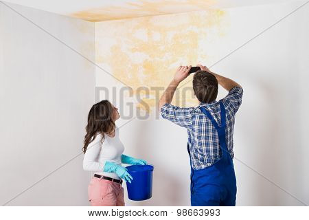 Handyman With Woman Photographing Water Damaged Ceiling With Mobile Phone At Home poster