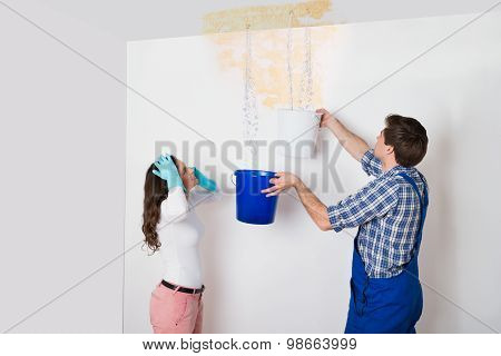 Woman With Worker Collecting Water From Ceiling In Bucket