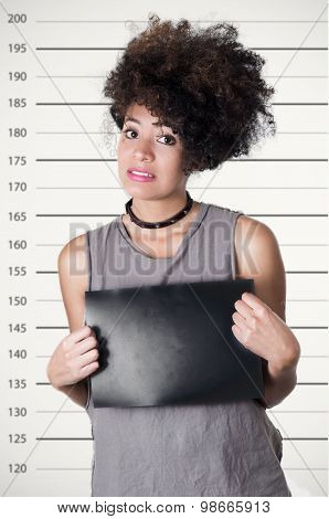 Hispanic brunette rebel model with afro like hair wearing grey sleeveless shirt holding up blank board as posing for mugshot, guilty facial expression. poster
