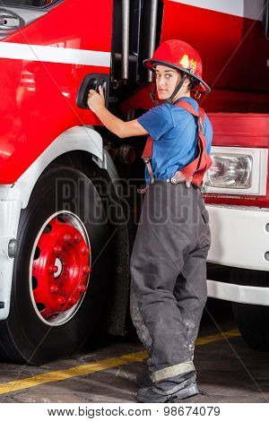Rear view portrait of confident firewoman standing by firetruck at station