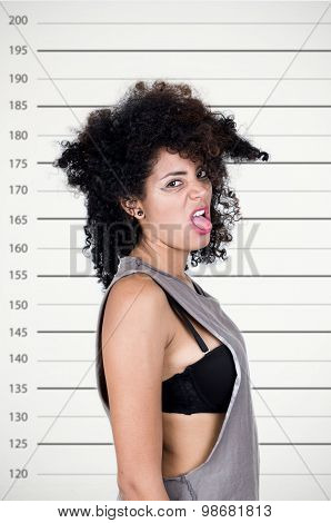 Hispanic brunette model with messy hair wearing grey sleeveless shirt looking unhappy into camera sh