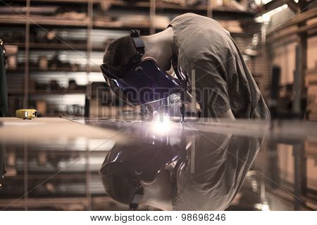 Worker welding aluminum using tig welder in factory poster