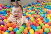 A cute crying girl sitting in a colorful ball pit at a playground. poster