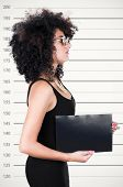 Hispanic brunette model with afro like hair wearing black sleeveless shirt holding up blank board as posing for mugshot concept from profile angle. poster