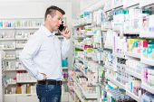 Confused mid adult man using mobile phone while looking at products in pharmacy poster