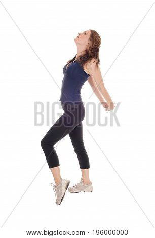 A young lovely woman in exercising outfit standing in profile and stretching after her exercise isolated over white background.