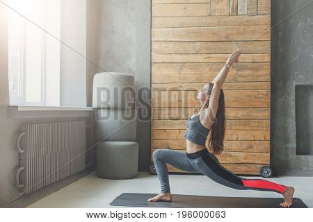 Woman in yoga class making asana exercises. Girl do warrior pose. Healthy lifestyle in fitness club. Stretching