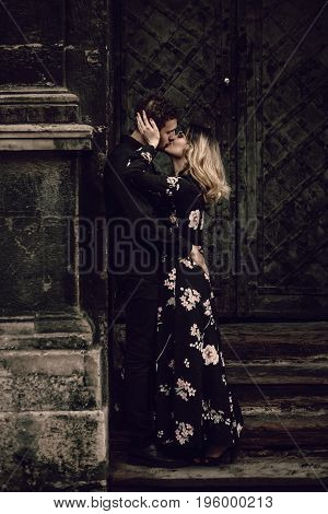 Stylish Gypsy Couple In Love Kissing In Evening City Street At Old Building. Woman And Man Embracing