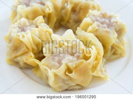 The close up of the Chinese steamed dumpling with pork on the white plate in the Chinese restaurant.(Select focus)