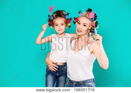 Funny family Mother and her child daughter girl with a paper accessories. Beauty funny girl holding paper crown on stick. Beautiful young woman holding paper crown on stick.