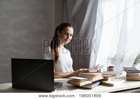girl reading a book and drinking coffee works at the computer