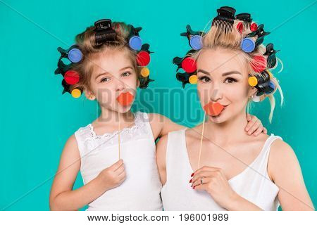 Funny family Mother and her child daughter girl with a paper accessories. Beauty funny girl holding paper lips on stick. Beautiful young woman holding paper lips on stick.
