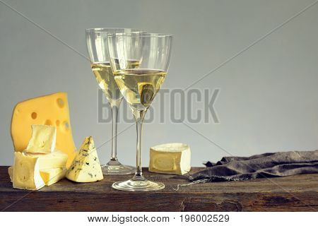 Wineglasses with white wine and various cheese cuts on vintage rustic table