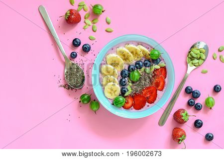 Berry smoothie bowl with chia seeds and pumpkin seeds view from above