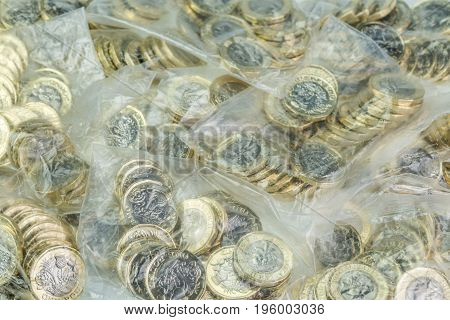 Money Bags Filled With British One Pound Coins.