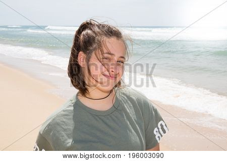 Above Angle Of Pretty Teenager Sitting On Sandy Beach
