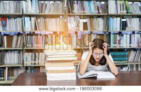 Young asian Girl with Glasses seriously with Her Exam and reading book in Library