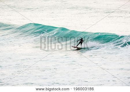 Surfing on turquoise wave in ocean. Surfer on wave