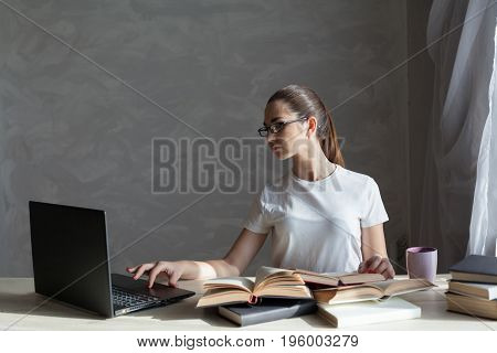 girl in library preparing for exams and reads books 1