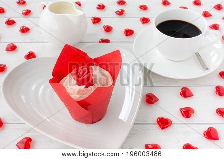 Valentines Cupcake decorated with a red rose on a white plate with a cup of coffee and milk jug in the background. White wooden background decorated with red acrylic hearts.