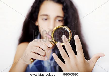 Little girl with a magnifying glass isolated on white background.