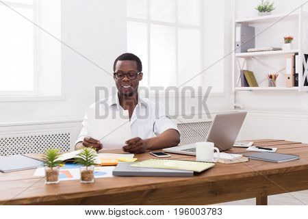 Happy black businessman in office. Successful employee at work with papers. Lifestyle portrait
