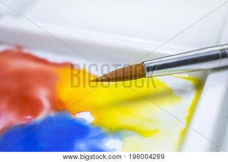 Watercolor paint brush on a white palette with the fluid paint merging together in an artist's studio
