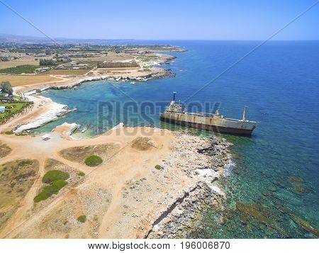 Aerial view of the abandoned ship wreck EDRO III in Pegeia Paphos Cyprus. The rusty shipwreck is stranded on the Peyia rocks at the kantarkastoi sea caves near Coral Bay in Pafos standing at an angle near the shore.