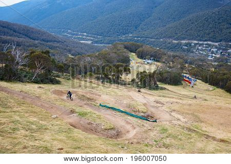 Mountain bikers descend down Thredbo on a cool autumn day in the Snowy Mountains, New South Wales, Australia