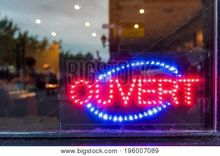 French ouvert open sign for store shop or restaurant glowing in the evening with window reflection