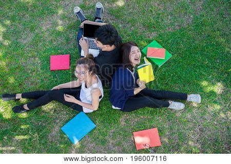 Young Students Group Smiling with Folders Book and Laptop computer Smiling on Grass in Education