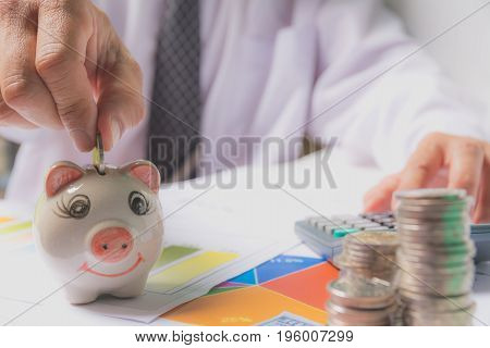 Hand of businessman holding coin and drop into the piggy bank. Stock financial indices with stack coin and businessman. Financial stock market in accounting market economy analysis.