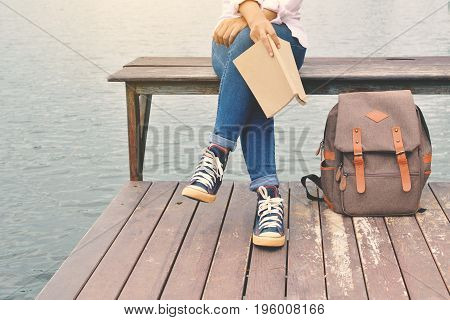 Happy Asian women reading a book and backpack in nature background Relax time on holiday concept travel color of hipster style