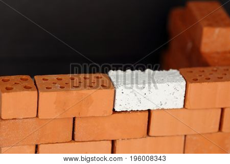 a red wall with one white brick as connection