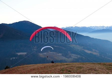 two paraglider are starting on a hill in the mountains