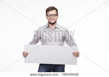 Young happy man portrait of a confident businessman showing presentation on a gray background. Ideal for banners, registration forms, presentation, landings, presenting concept.