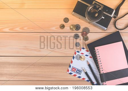 Preparation For Travel Concept With Camera, Coin, Envelope, Notebook And Copy Space On Wooden Table