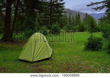 Green camping marquee on пдфву in forest in Altai mountains. Altay Republic Siberia Russia.