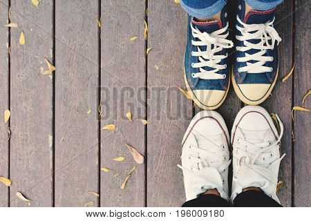Feet of lover on old wooden background color of hipster tone concept affection