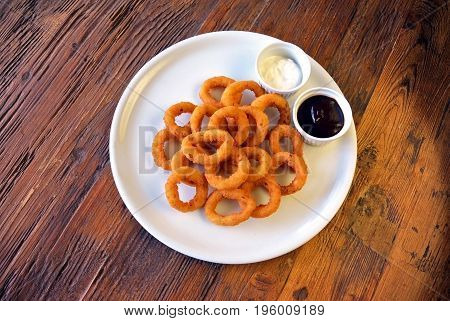 white plate with Homemade Crunchy Fried Onion Rings and sauces on wooden table background, top view