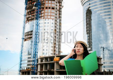 Asian Woman In A Blue Dress And White Protective Helmet. Engineer Supervises Inspection And Control