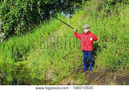 Boy Fishing On A Pond