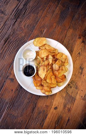 White plate with homemade potato chips on a wooden background, top view. Salty crisps with sauce on a rustic table