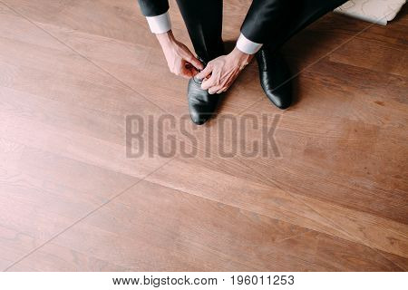Business man tying shoe laces on the wooden floor. Groom getting ready in the morning before the wedding. Top view