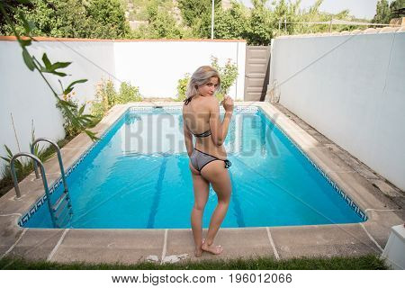 Young girl in bathing suit looking at swimming pool before bathing. She's on her back.