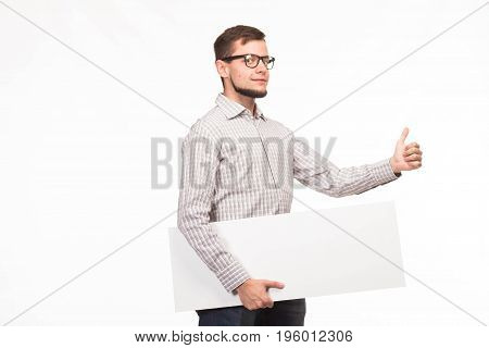 Young sexy man portrait of a confident businessman showing presentation, pointing paper placard gray background. Ideal for banners, registration forms, presentation, landings, presenting concept.