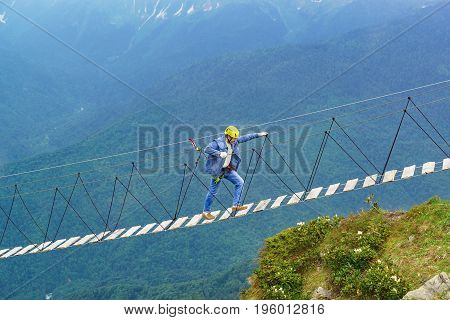 An elderly man in a denim suit helmet and rescue ropes is a rope bridge high in the mountains. Cloudy summer day