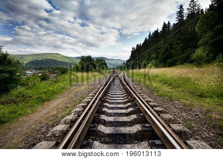 Railroad going into the distance Against Mountains And Beautiful Cloudy Sky Near Forest. Landscape With Railway.
