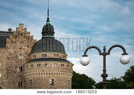 Old medieval castle in Orebro Sweden Scandinavia Europe. Landmark in foreground and blue cloudy sky in background. Architecture and travel.
