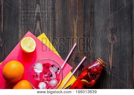 Bottle with fresh lemonade, fruits and ice cubes on wooden background top view.